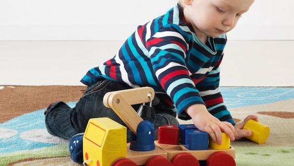 Batole si hraje s červeným, modrým a žlutým dřevěným jeřábem IKEA MULA na zeleném a modrém koberci pro děti.