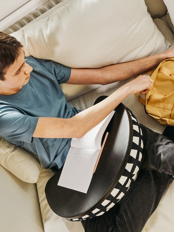A teenager sitting on a sofa with a BYLLAN laptop support holding a book getting something out of a yellow STARTTID backpack.