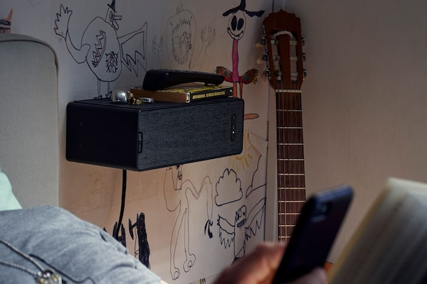 Ein SYMFONISK Regal-WiFi-Speaker an einer mit Graffiti bemalten Wand eines Schlafzimmers, im Hintergrund ist eine Gitarre, im Vordergrund ein Bett zu sehen.