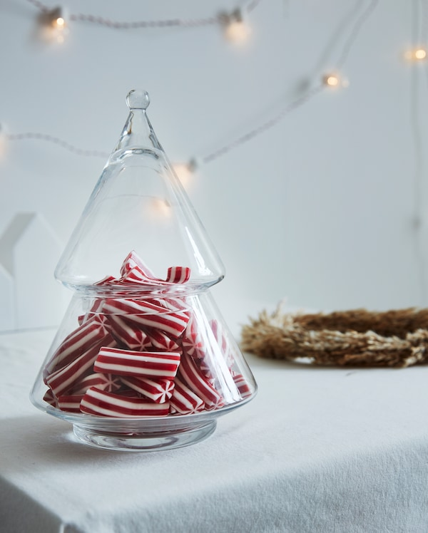 Clear glass VINTERFEST serving bowl filled with red and white striped candy on a white table cloth.