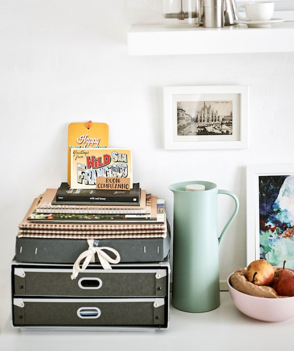 A desk organizer, flask, fruit bowl and pictures arranged as a pretty display.