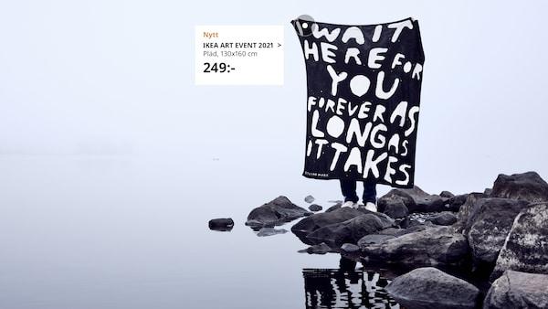 En person håller upp en pläd med ett budskap på från kollektionen IKEA ART EVENT 2021.