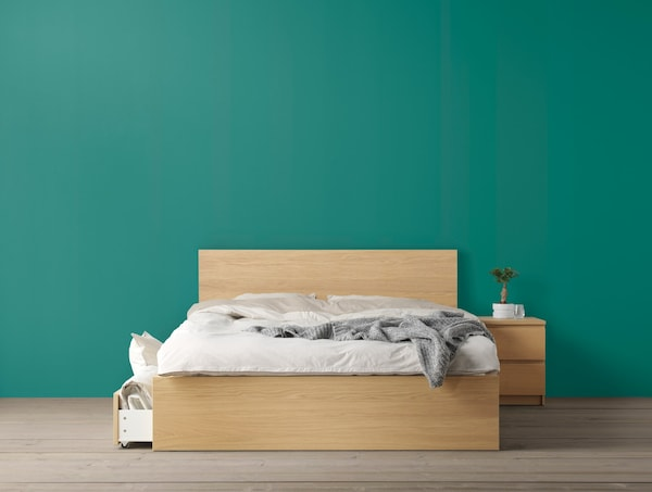 A green wall with a natural wood bed frame and white bedlinen