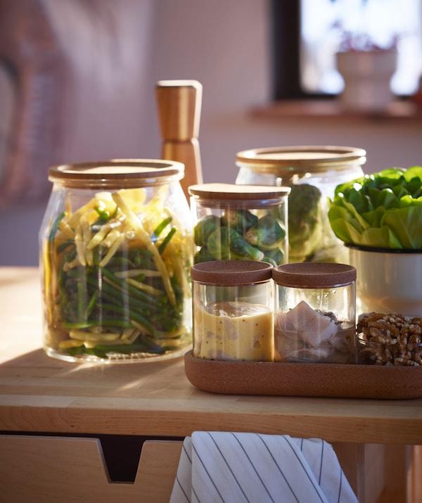 Vários acompanhamentos maiores e mais pequenos – vegetais, arenque e outras coisas – em frascos de vidro de diferentes tamanhos, sobre uma superfície de madeira.