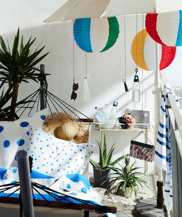 Beach-inspired balcony with hammock and stand, and a parasol with everything from sunglasses to LED lamps hung from it.