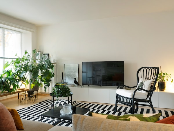 Beautiful open-plan living room with IKEA wicker chair and IKEA carpet.