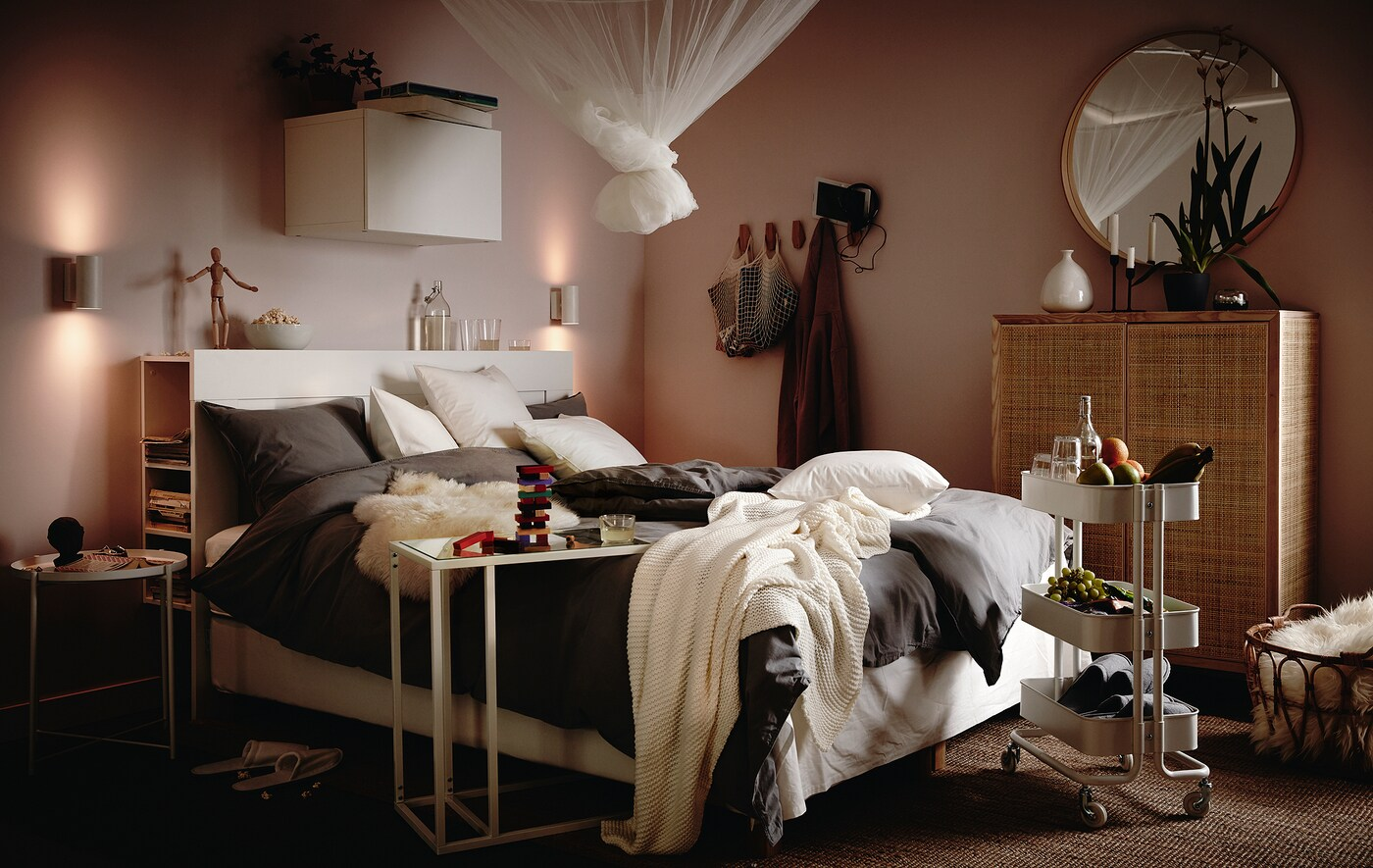 Bed laden with fluffy bedding, cushions and throws, trolley with snacks and drinks beside it, and a net in a knot hanging above.