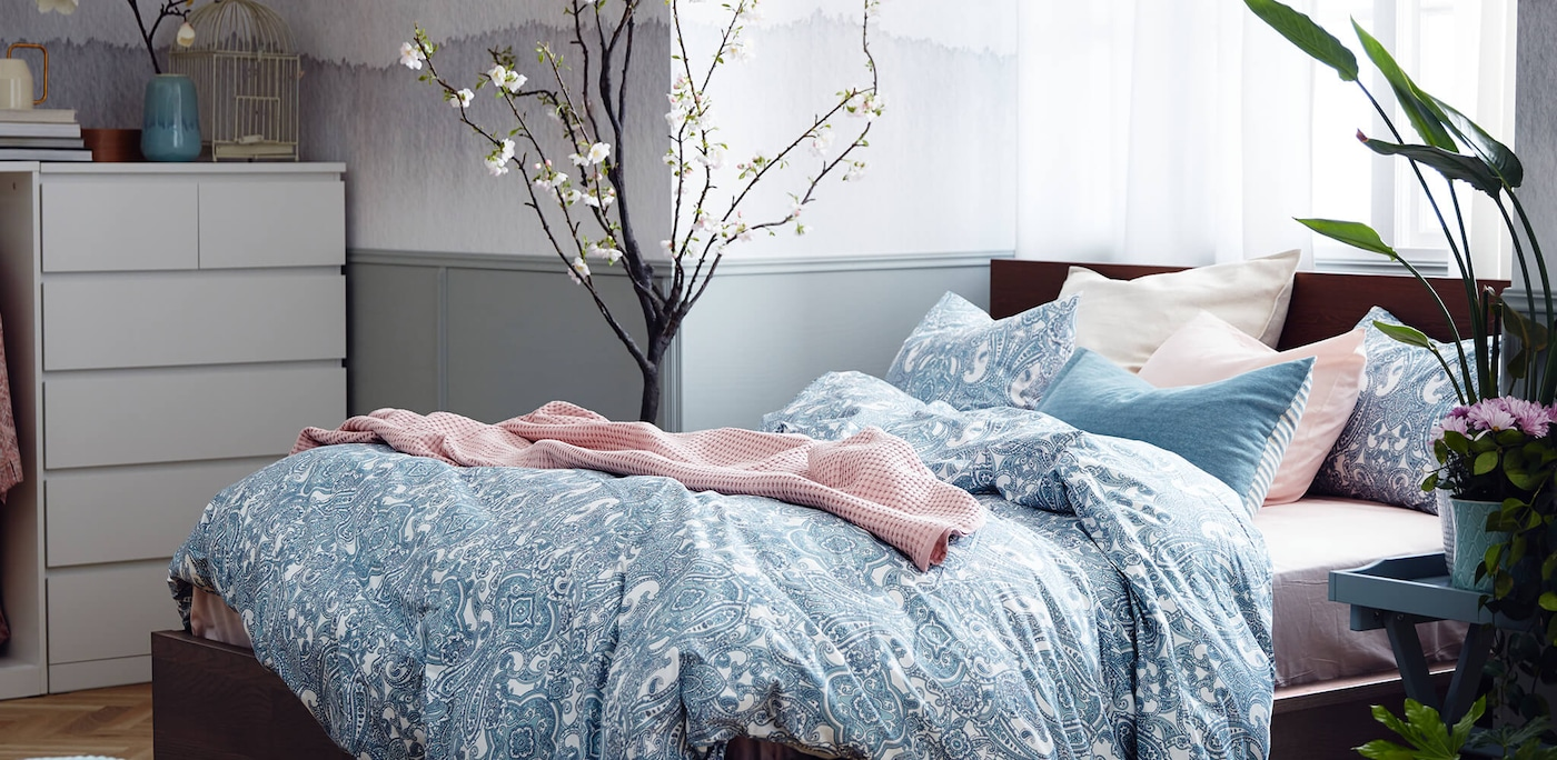 Bed with blue and white patterned duvet cover and pink blanket with plants on each side