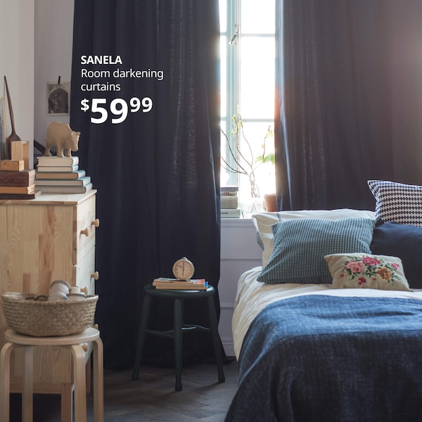 Bed with several pillows in a sunny room with books stacked on dresser. SANELA Room darkening curtains- $59.99