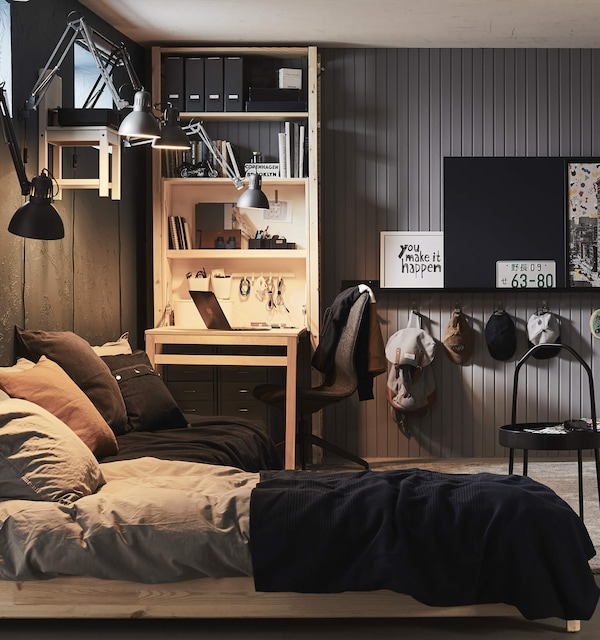 Bed with sheets pulled back and a lamp above it in a room with small desk and shelves