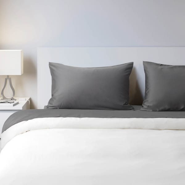 Bed with two pillows  next to a nightstand and lamp