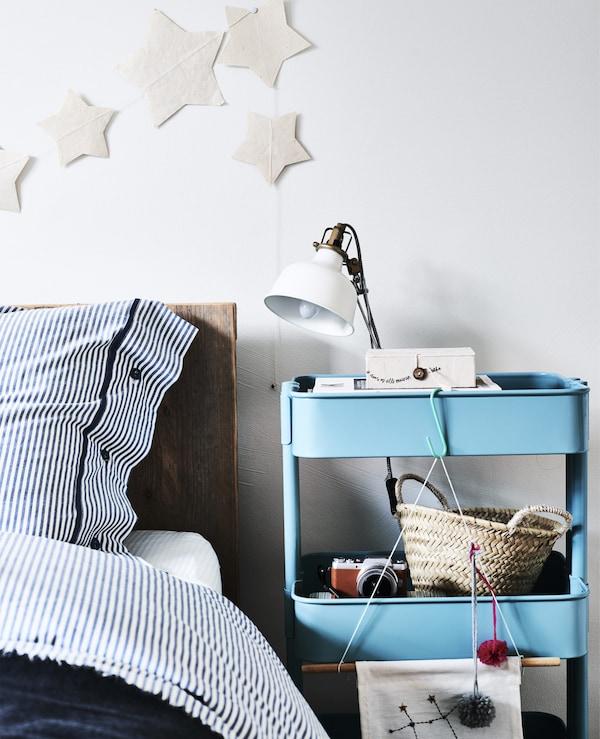 ベッドサイドテーブルとして使われているブルーのワゴンとランプ。