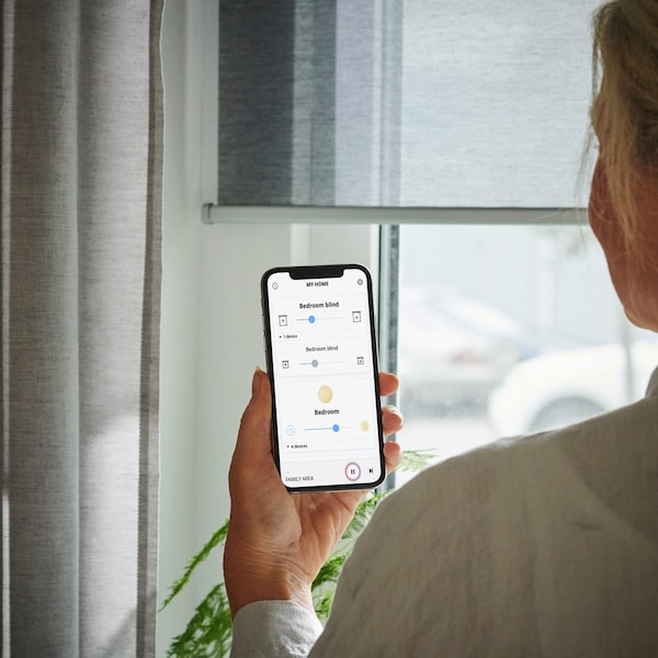 Bedienung des KADRILJ Rollos mit der IKEA Home smart App vor einem Fenster mit Ausblick.