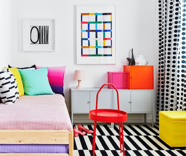 Bedroom furnished in a style characterized by block coloring and graphic patterns. Bed with cushions, EKET cupboards by it.