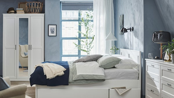 Bedroom in blue and white, with accessories in various textures to add interest.