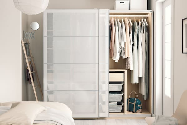 Bedroom in light colours with a PAX wardrobe half opened