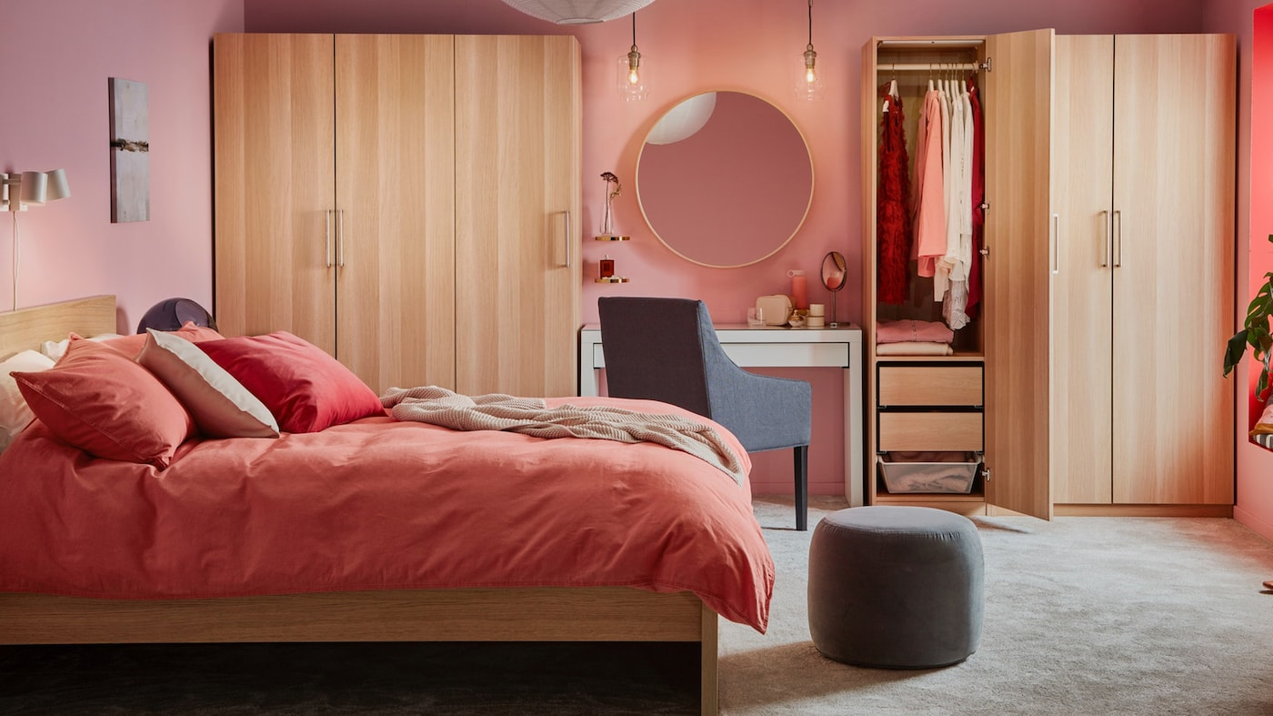 Bedroom in warm tones with pink walls, MALM bed and PAX wardrobes.
