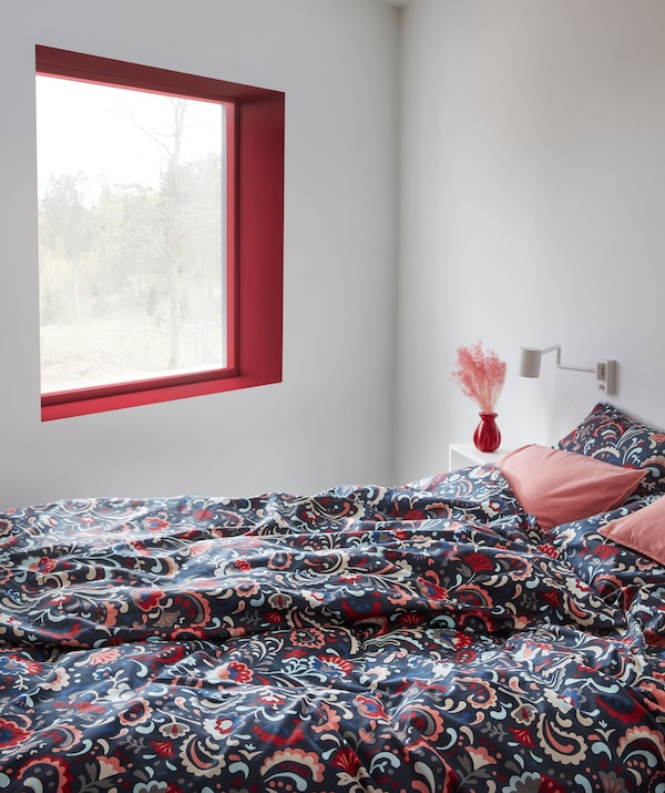 Bedroom interior and a bed made with bed linen in bright colours and decorated with a traditional Swedish kurbits pattern.