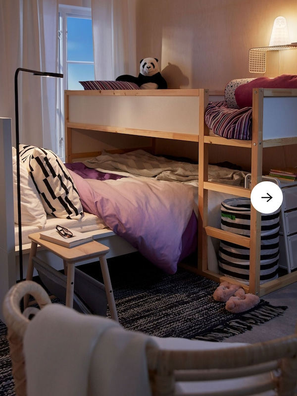 Bedroom interior with a loft bed standing across a lower bed.