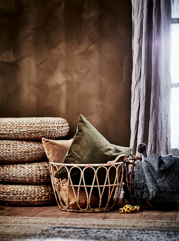 Bedroom section in earthy-brown colour scheme: SNIDAD rattan baskets with textiles, ALSEDA stools and natural-material rugs.