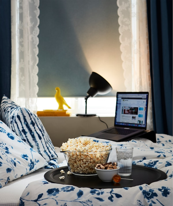 Bedroom turned simple film theatre; laptop on a stand, lowered black-out blind, lit lamp facing away, snack tray on the bed.