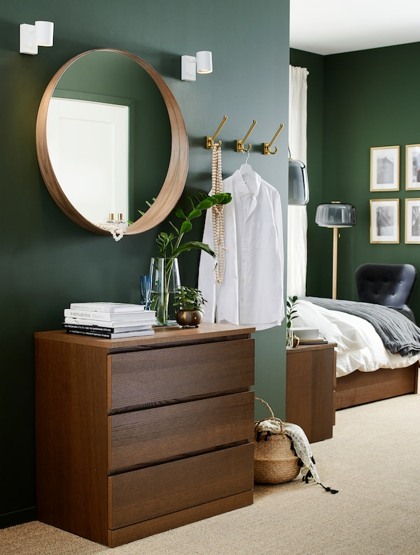 Bedroom with a chest of drawers in brown stained ash veneer, a round mirror, a seagrass basket and hooks.