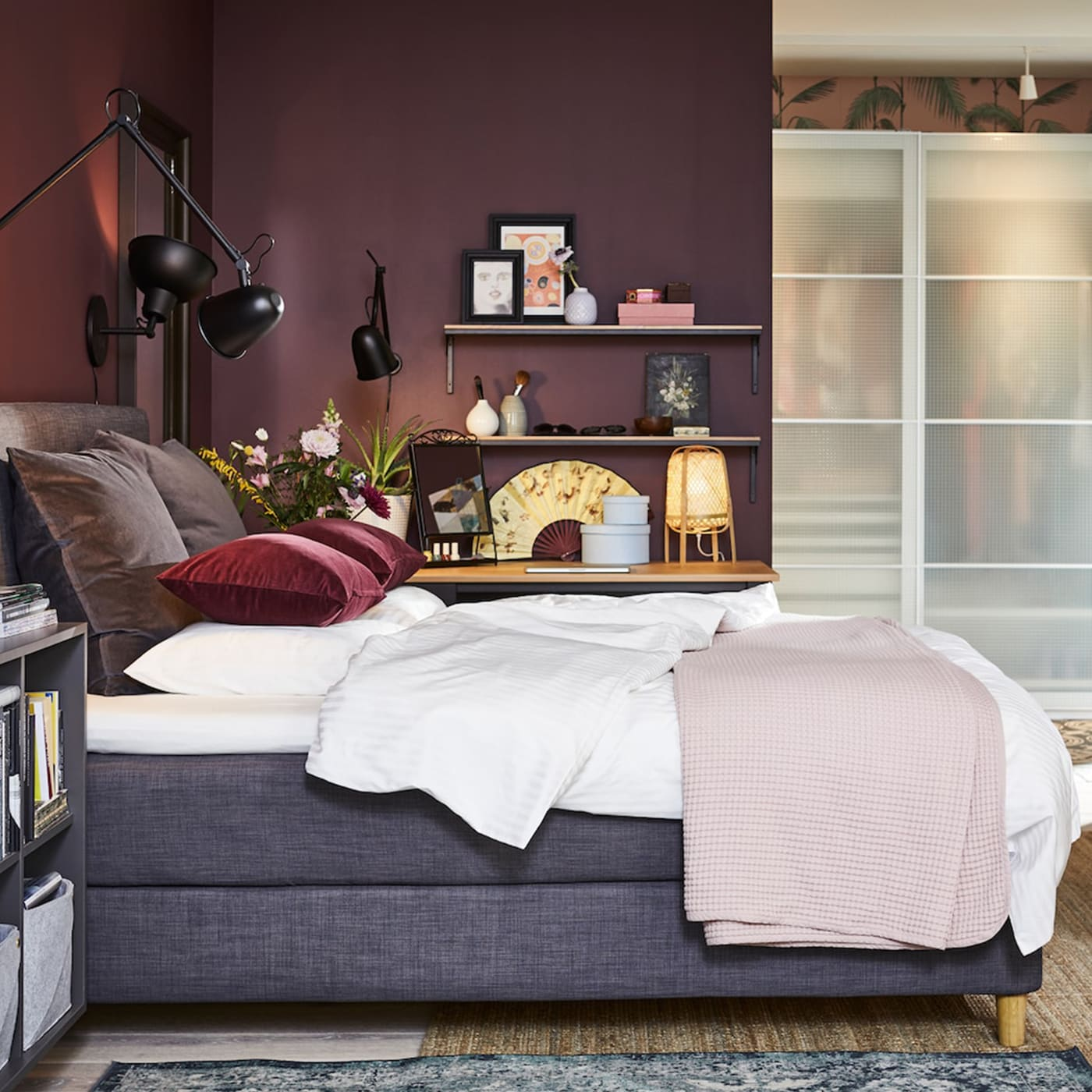 Bedroom with a dark grey divan bed, black wall lamps, a jute rug, a black-brown chest of drawers and dark red cushion covers.