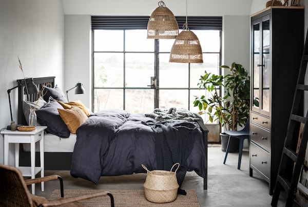 Bedroom with a dark HEMNES bed placed centre, French windows along one wall, and details in natural materials and colours.