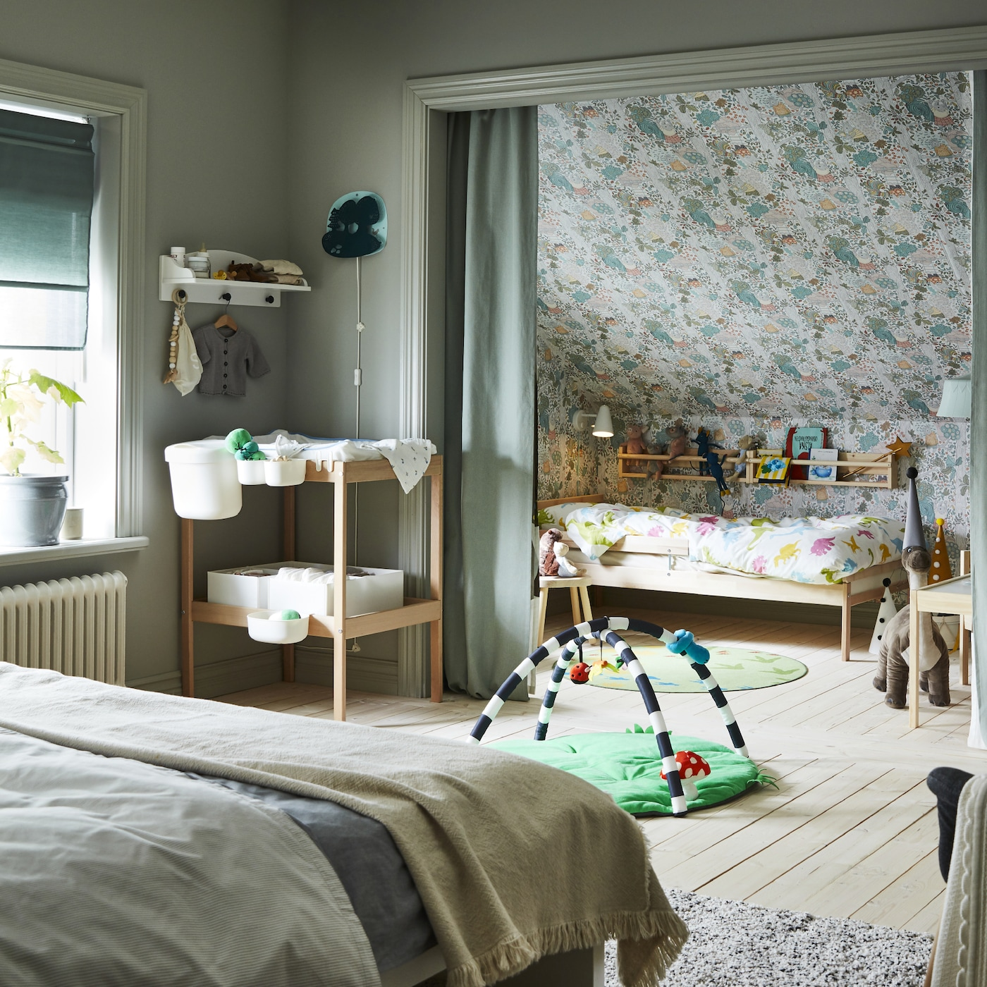 Bedroom with a double bed, a changing table and baby accessories. A children's bed stands in an alcove behind green curtains.