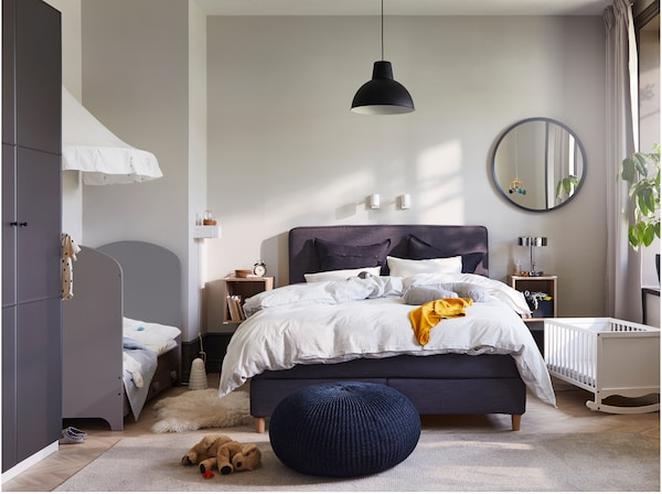 Bedroom with a grey cot, a white cradle, a dark grey divan bed, a dark blue pouffe, a round mirror and white wall lamps.