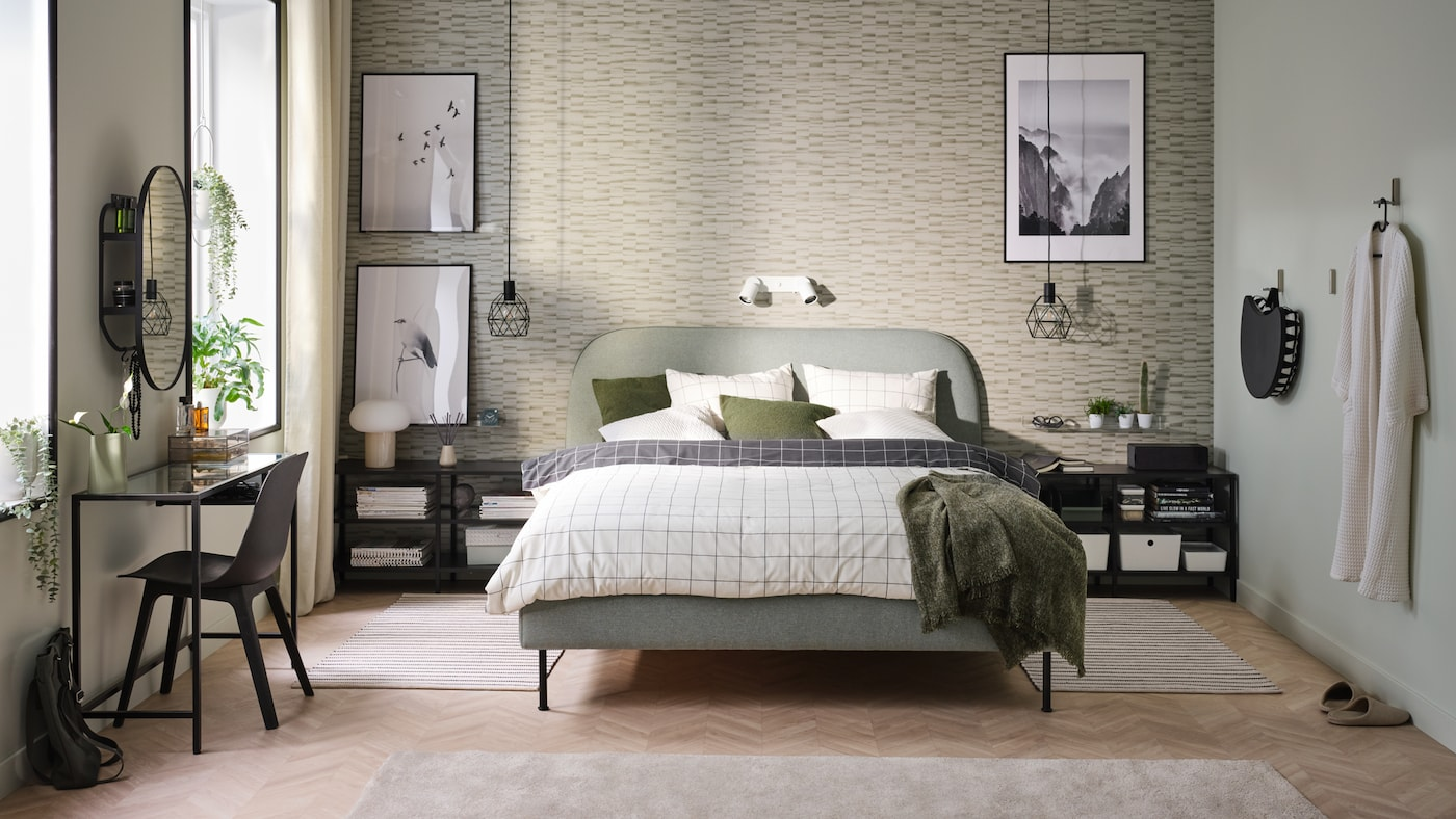 Bedroom with a HEMNES bed frame, pillows, bedcovers and some clothes randomly thrown on the bed. Large window in the background and tables to the right.