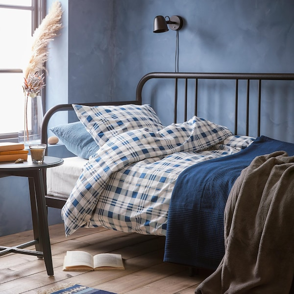 Bedroom with a metal twin bed, blue walls and blue plaid duvet cover.