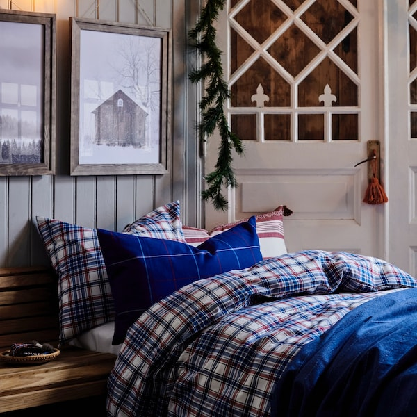 Bedroom with a wood cabin feel, flannel quilt and pillows in a blue pattern.