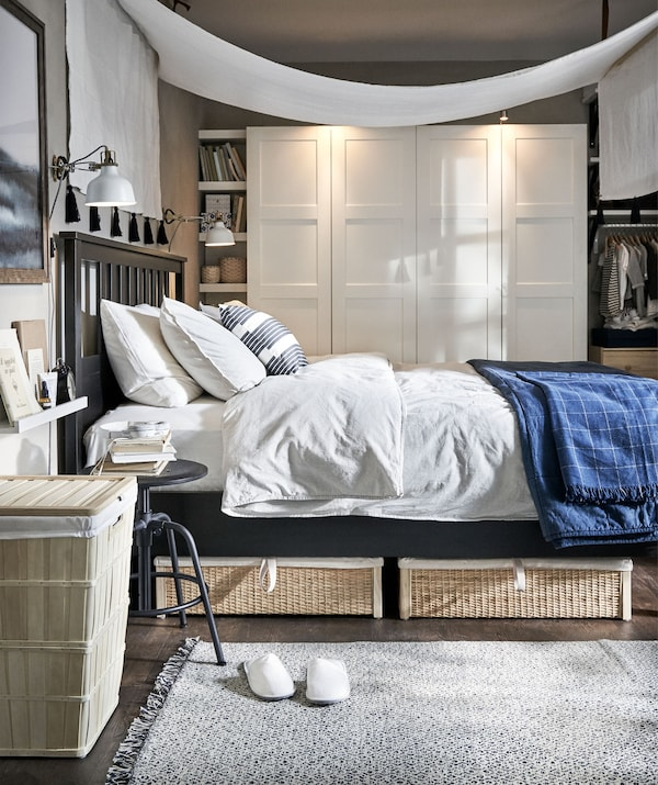 Bedroom with airy feel, natural materials and a simply arranged canopy hung over the bed. Wardrobe along the back wall.