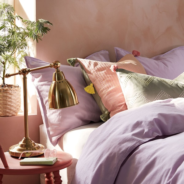 Bedroom with pale purple bed linens, handmade cushions, and a brass table lamp.