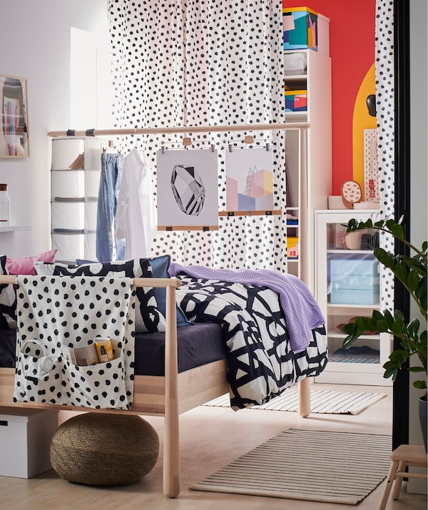 Bedroom with the far wall, behind curtains, covered with open and closed storage. The high headboard of a bed acts as room divider.