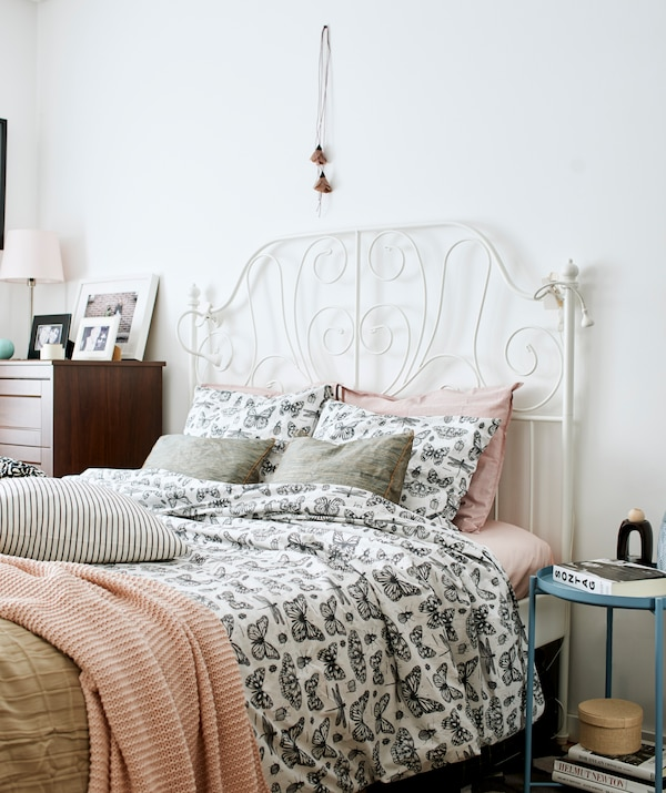 Bedroom with white, wrought-iron bed made up with butterfly-patterned bedding and pink covers, and dark wood drawers.