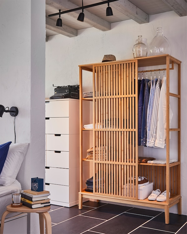 Behind a bedroom wall stands a NORDKISA open wardrobe in bamboo, the sliding door is centred and shows clothes on a rail.