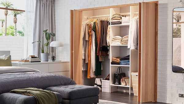 Beige closet curtains are opened to reveal an AURDAL closet organizing system. There are areas for hanging clothes and for folded clothes as well as a laundry basket.