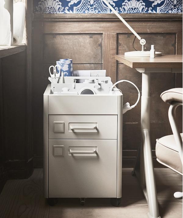 Beige lådhurts i metall intill ett skrivbord samt kontorstillbehör i en prydlig låda högst upp.