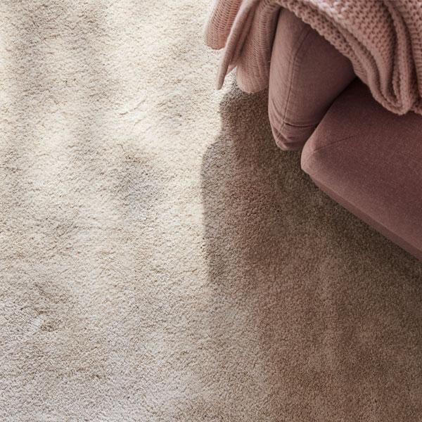 Beige nukkamatto, vaaleanpunainen sohva ja huopa näkyvät kuvan reunassa.