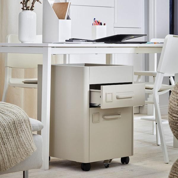 Beige säilytyslipasto työhuoneessa valkoisen pöydän alla.