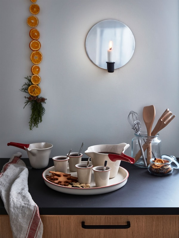 Beige stoneware mugs and jugs with mulled wine are placed on a black counter while a candle hangs on a wall sconce.