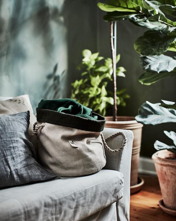 Beige vattentät planteringskasse med tvinnade jutehandtag visas i en grå soffa intill stora växter.