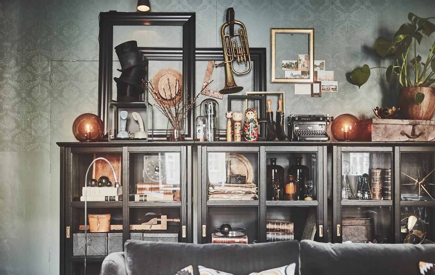 Beirazko atea duen IKEA MALSJÖ kabinetea, oroimenez, pitxerrez, liburuz, marko eta kaxaz beteta.