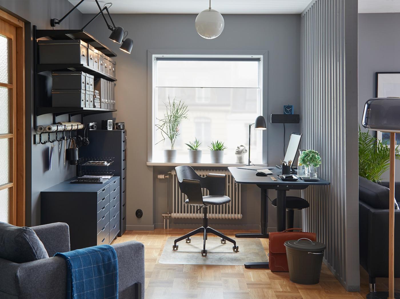 BEKANT مكتب جلوس/وقوف أزرق/أسود بمشمع ضمن مساحة عمل ذات ألوان منسقة في مكتب منزلي مع كرسي اجتماعات وتخزين.