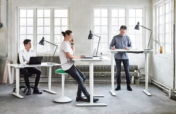 BEKANT sit/stand desks in three different positions with one man sitting on an office chair, one man on a taller stool and another standing.