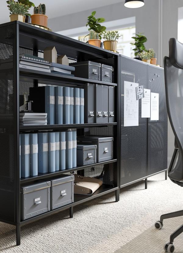 BEKANT وحدة رفوف مكتبية سوداء من ايكيا تُستخدم كمقسم، مع ملصقات تذكير ملصقة ببابها ذو المشبك المغناطيسي.