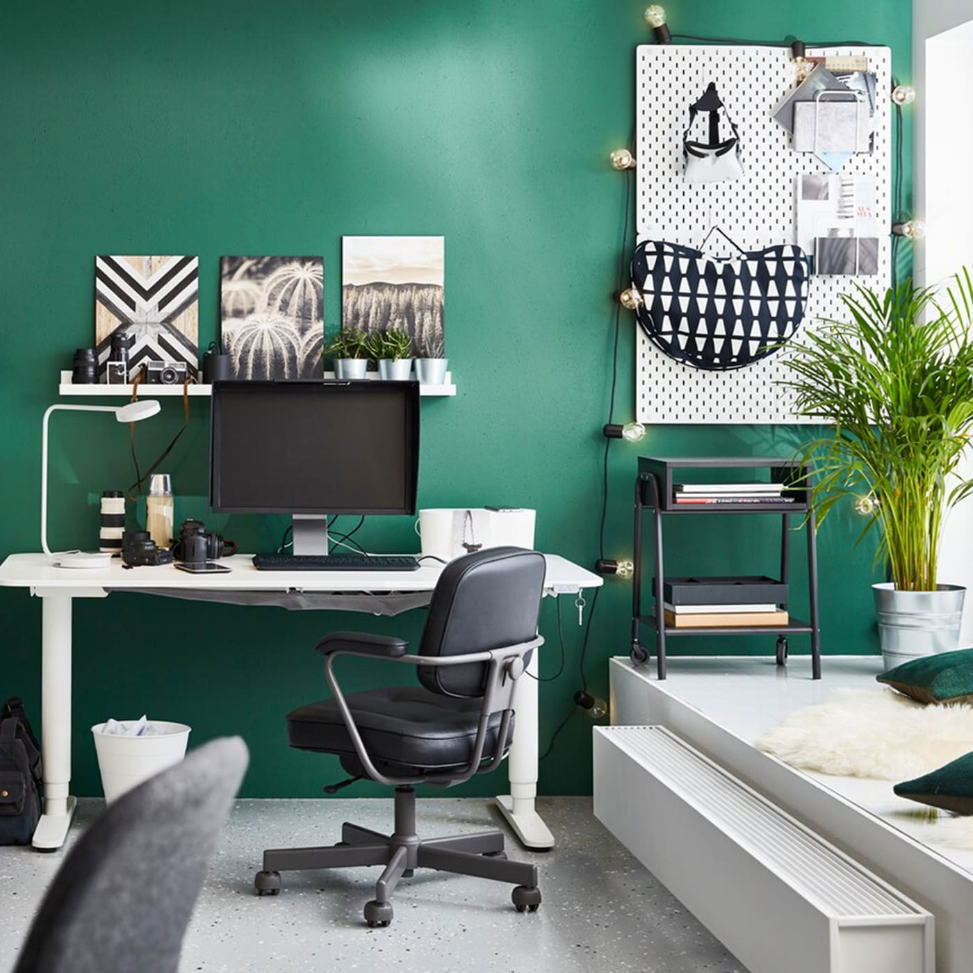 BEKANT white sit-stand desks in a green-walled office space with aALEFJÄLL black swivel chairs and NILSERIK stool.