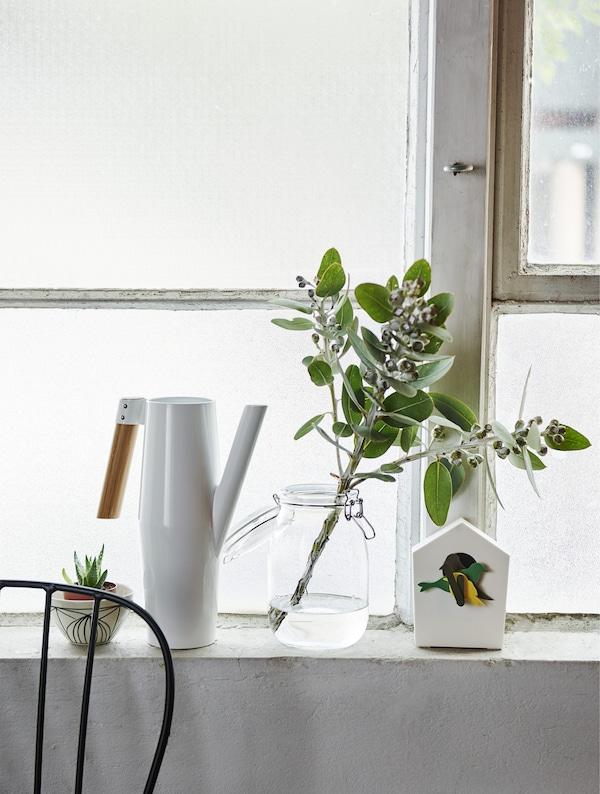 Bela kantica za zalivanje i čaša s biljkama na prozorskom simsu.
